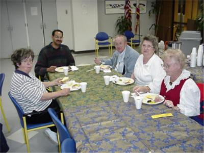 Coin club members eating and enjoying the benefit of coin club membership